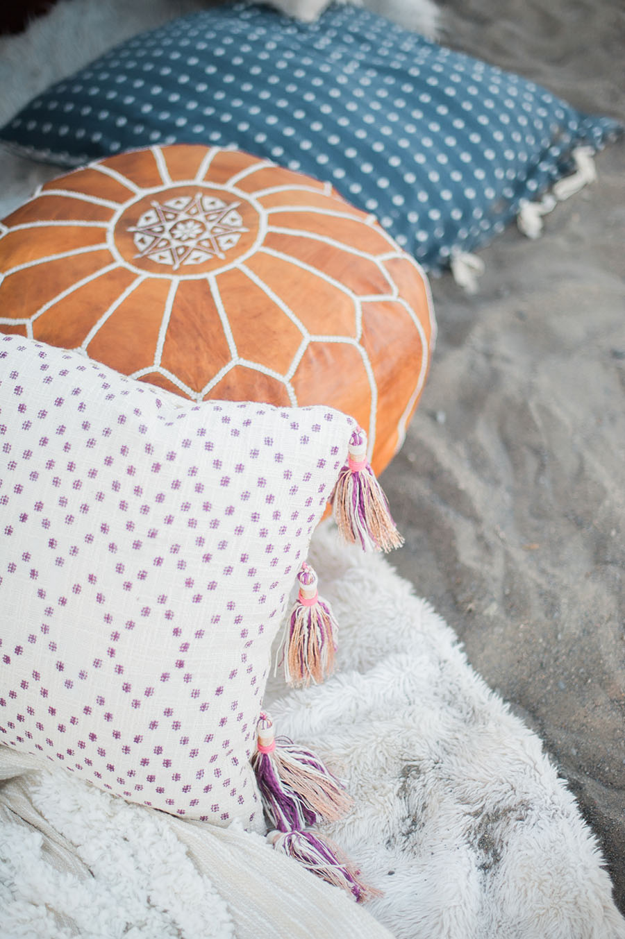 Boho inspired beach picnic with throw pillows and pouf